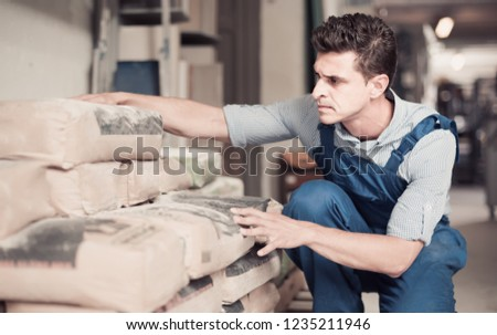 interested male in uniform is choosing cement in the building store room