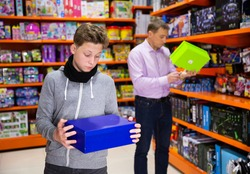 Interested teenager shopping in store of kids toys, choosing new plaything for gift