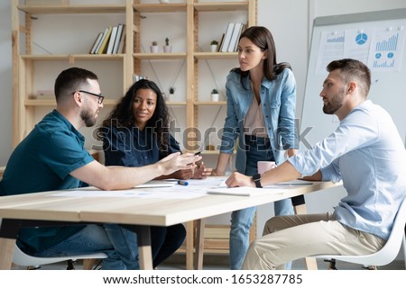 Interested young multiracial colleagues with female team leader listening to skilled coworker in glasses in modern office. Focused mixed race business people company employees discussing project.
