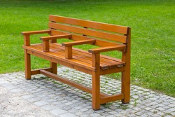 Interestin unusual wooden park bench at a park, divided on three part