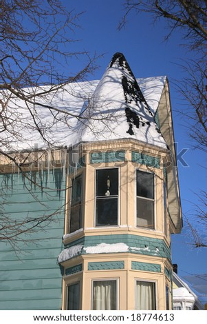 Interesting architectural detail of an older home covered in snow.