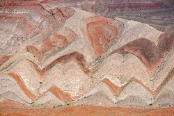 Interesting background of red banded strata viewed from Highway 163. The zigzag pattern is result of erosion of the tilted strata. Mexican Hat, Utah - USA