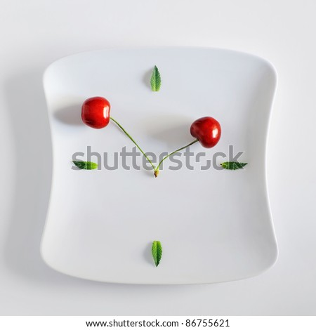 interesting clock dial made of a plate, green leaves and clock hands made of cherries