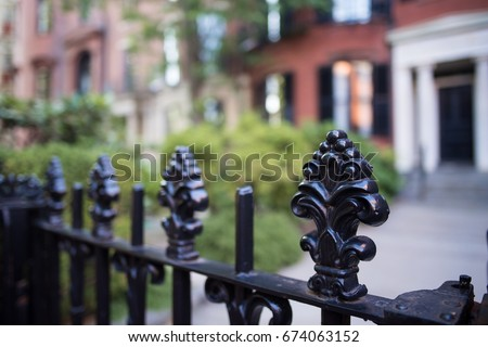 Interesting iron fence with intricate carving with an antique, colonial style, in the Beacon Hill neighborhood in historic Boston.