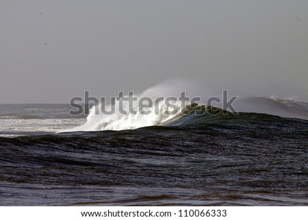 Interesting long big Atlantic white crashing wave in a stormy day