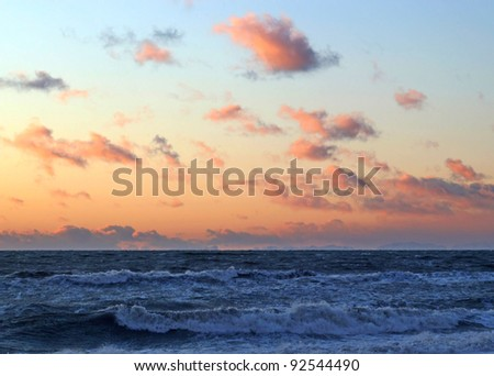 Interesting orange clouds at sunset over the ocean waves.