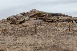 Interesting rock formations on side of rural road with vintage barbwire fence on overcast day in New Mexico