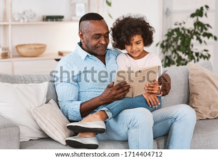 Interesting stay home pastimes. Pretty African American girl listening to her grandfather read book in living room Foto stock ©