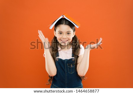 Interesting story for kid. Studying and relaxing. Study at home. Homework concept. Homeschooling and private lesson. Book on her head. Little girl book roof head. Small girl book orange background.