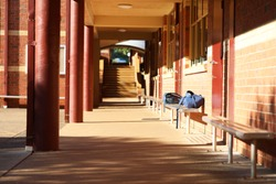 Interesting view of school buildings and outdoor yard with bricks, steps, stairs, pillars and seats. School bags backpacks duffle bags on a bench seat outside classrooms. Typical high school