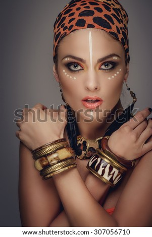 Interesting woman in leopard pattern bandana with art make up posing in studio. Isolated on grey background.