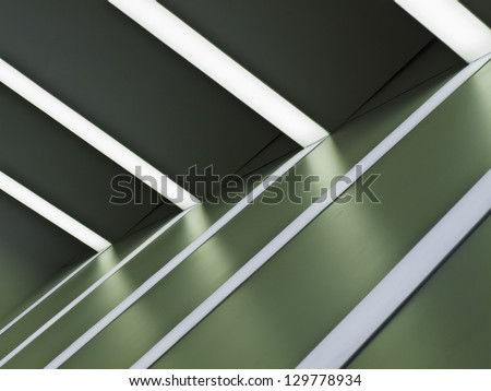 Interior abstract: Ceiling lights and white stripes on green wall at auto show