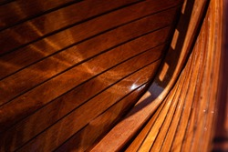 Interior abstract view of a traditional yacht constructed of highly varnished wooden planks with black caulking. Shows the construction of a craft. Beautiful red wooden tones, with interesting light