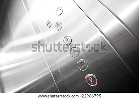 Interior and closeup of metal buttons in elevator - stock photo