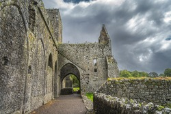 Interior and exterior of ruined and abandoned Hore Abbey with dramatic storm sky. Located next to Rock of Cashel castle, County Tipperary, Ireland