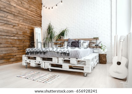 Interior apartment decoration design with wooden pallets bed, furniture, plant in vase, retro camera and guitar. Creative comfortable business building concept.