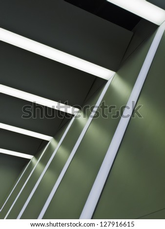 Interior architectural abstract: Ceiling lights and white stripes on green wall