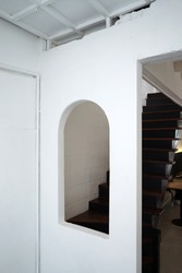 Interior architecture and design of white room decorated with curve window and wooden antique staircase