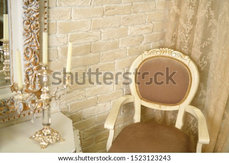 Interior. Beautiful beige chair is in a beige room, near the table there is a candle holder #1523123243