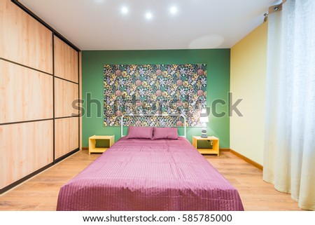 Interior bedroom with a large double bed with bedside tables, picture on the wall on a background of modern wallpaper #585785000