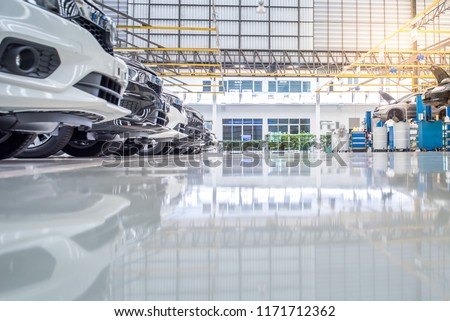 interior car-care center. The electric lift for cars in the service put on the epoxy floor in new car factory service