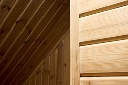 Interior carpentry background. Softwood clapboard, batten, plank timber blockhouse plank, or plank beam background with copyspace. Corner of rustic room finished with blockhouse or clapboard.