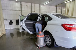 Interior cleaning with an industrial vacuum cleaner of a modern car in a car wash hangar.