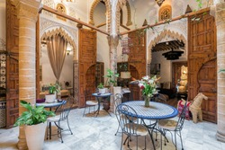 Interior courtyard of a stunning traditional Moroccan riad, with arched doorways, wooden doors, stucco details, tables and chairs, indoor plants and marble floors