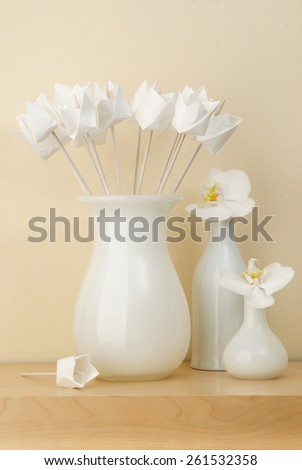 interior decoration origami tulips in a white vase on a shelf with white orchid flowers in vases near
