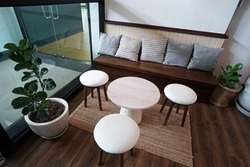 Interior design and decoration of living area -decorated with indoor green plant pots ,wooden bench and cushion sofa set