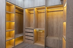 Interior design decor furnishing of luxury show home bedroom showing walk in wooden wardrobe closet furniture
