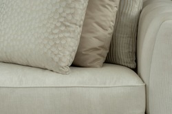 Interior design detail of silk cushions with a feathered pattern and gold textures on a silk couch.