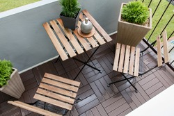 Interior design. Interior shots of a balcony with plants, table and chairs.
