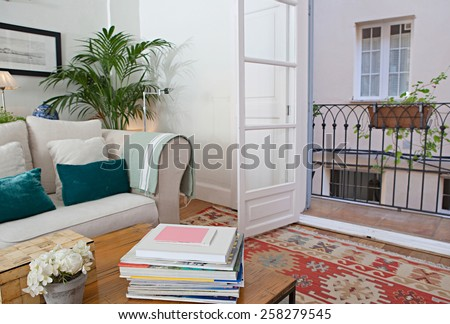 Interior design lifestyle of a home living room with white sofa and cushions, interior view. House indoors with carpets and open french doors balcony. Tranquil and aspirational lifestyle home space.