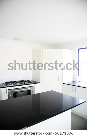 Interior design of a kitchen with black benchtop and white cupboards.