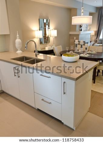 Interior design of a luxury modern kitchen with the dish with some pears on the counter and the dining room at the back.. I