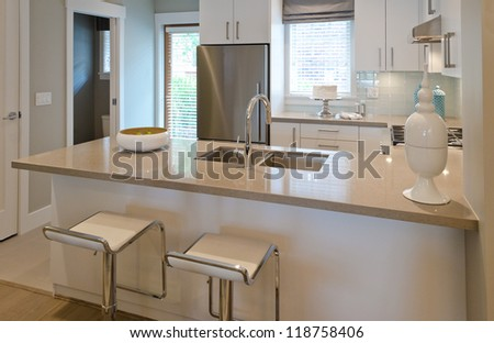 Interior design of a luxury modern kitchen with two sits and the dish with some pears on the counter. I