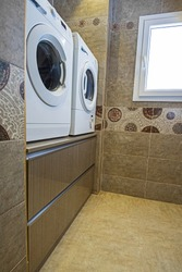 Interior design of a luxury show home bathroom utility room with washing machine dryer and cupboard