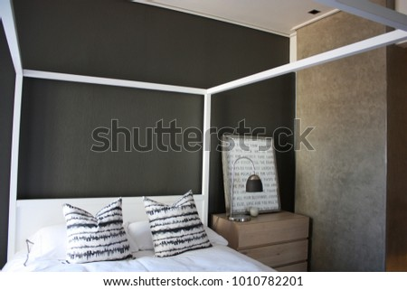 Interior design of a modern bedroom, with a white 4 poster bed and dark grey wall