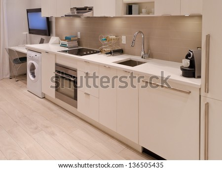 Interior design of a modern kitchen, in combination with laundry and the office room. For small condos.