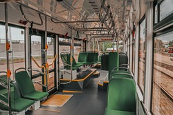 Interior design of a modern tram. Empty tram interior. Public transport in the city. Passenger transportation. Tram with green seats and metal handrails.