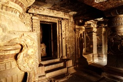 Interior design of ancient Indian stone temple, Ajanta caves (rock-cut Buddhist cave monument). Beautiful carved wall and pillars.