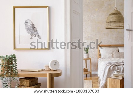 Interior design of bedroom with mock up picture frame, wooden console, plants, clock, coffee table, rattan decoration and elegant accessories in stylish home decor.
