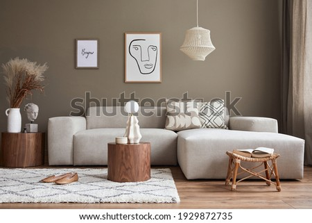 Interior design of cozy living room with stylish sofa, coffee table, dired flowers in vase, mock up poster, carpet, decoration, pillows, plaid and personal accessories in modern home decor. Template.