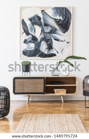 Interior design of living room at nice scandinavian apartment with modern commode, lamp, abstract paintings, plants, tropical leafs and elegant accessories. Modern home decor. Template. Mock up.