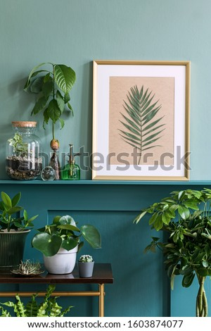 Interior design of living room with gold mock up photo frame on the green shelf with beautiful plants in different hipster and design pots. Elegant personal accessories. Home jungle. Template.