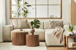 Interior design of living room with stylish modular beige sofa, wooden coffee tables, plants, pillows, plaid, neutral room divider, decoration and elegant accessories. Modern home decor. Template.