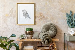 Interior design of living room with wooden bench. plants, cacti, pillow, plaid, rattan basket, gold mock up poster frame, books and elegant presonal accessories in modern home decor.