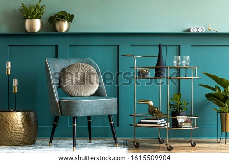 Interior design of luxury living room with stylish armchair, gold liquor cabinet, a lot of plants and elegant personal accessories. Green wall panelling with shelf. Modern home decor. Template.  Photo stock ©