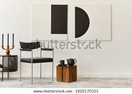 Interior design of modern living room with black stylish commode, chair, mock up art paintings, copy space, decorations and elegant accessories in home decor. Template.